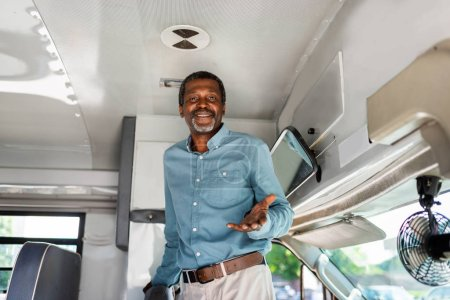happy mature african american bus driver standing inside bus and looking at camera