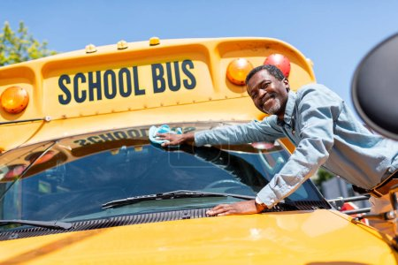 smiling mature african american bus driver wiping front window of school bus and looking at camera