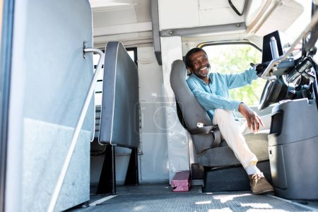 Photo for Happy mature african american bus driver looking at camera while sitting inside bus - Royalty Free Image