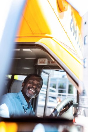 happy mature african american bus driver looking at camera