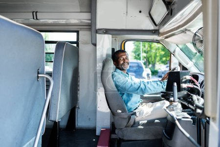 Photo for Mature african american driver sitting at bus and looking at camera - Royalty Free Image