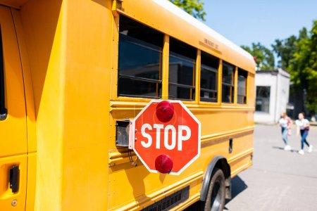 Photo pour Vue partielle de l'autobus scolaire avec panneau d'arrêt debout sur le parking avec des élèves flous courant en arrière-plan - image libre de droit