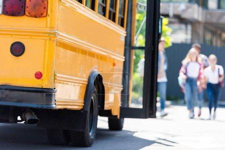 Photo pour Traditionnels les autobus scolaire américain avec groupe d'étudiants marche floue sur fond - image libre de droit