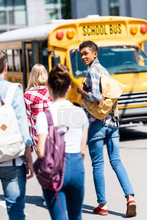 rear view of handsome teen african american schoolboy walking to school bus with his classmates and turning back at camera