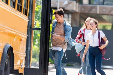Photo pour Heureux élèves adolescents en cours d'exécution en autobus scolaire - image libre de droit