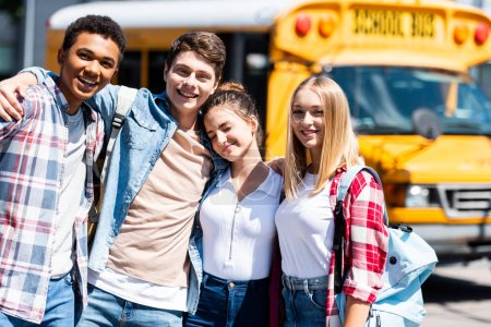group of teen happy scholars looking at camera and embracing while standing in front of school bus
