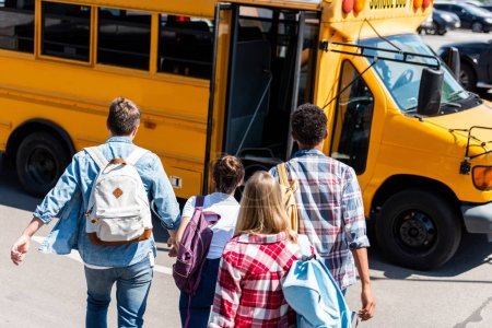 Photo for Rear view of group of teen students walking to school bus after school - Royalty Free Image