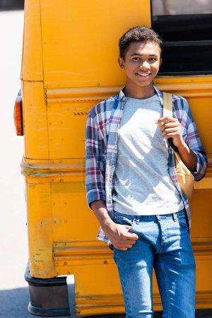 happy teen african american schoolboy leaning back on school bus