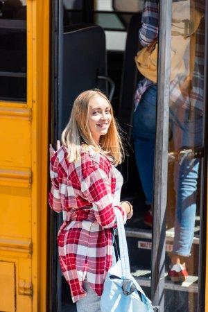 happy teen schoolgirl walking into school bus and looking back at camera