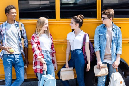 group of teen scholars leaning back at school bus and looking at each other