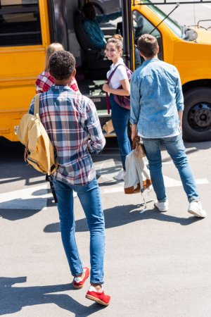 rear view of group of teen scholars walking to school bus after school