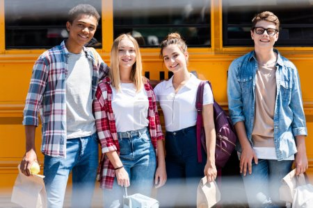 group of teen happy scholars looking at camera while standing in front of school bus