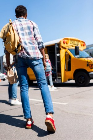 rear view of teen schoolboy walking at school bus