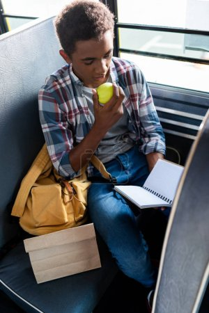 teen african american schoolboy reading apple while holding blank notebook