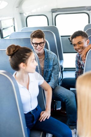 group of teen scholars riding school bus and chatting