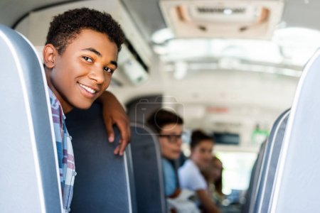 teen students sitting at school bus and looking back at camera