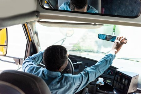 Photo for Mature african american driver adjusting back view mirror at bus - Royalty Free Image