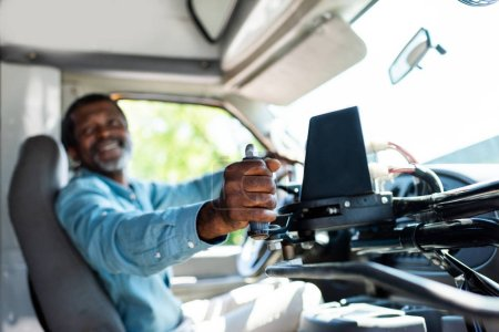 Photo for Mature african american bus driver pulling lever at bus - Royalty Free Image