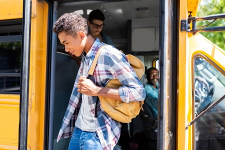 african american student walking out of school bus while driver looking at him