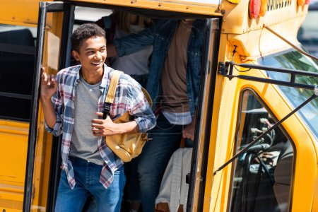 african american happy student walking out of school bus with classmates