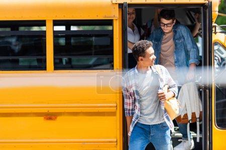group of teen scholars walking out of school bus