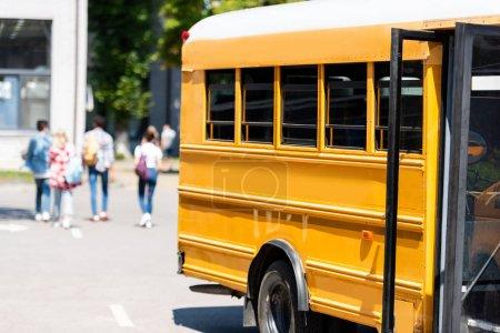 Photo pour Autobus scolaire traditionnel debout sur le parking avec des élèves flous marchant sur le fond - image libre de droit
