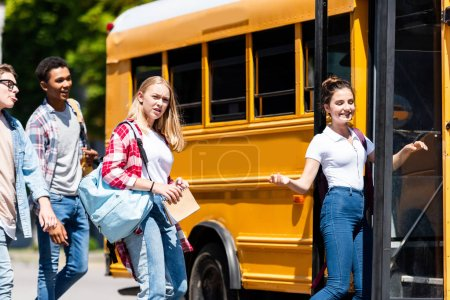 group of teen students entering school bus after lessons