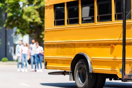 partial view of school bus standing on parking with blurred students walking on background