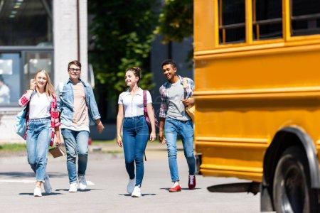 Photo pour Groupe de jeunes chercheurs marchant derrière le bus scolaire sur le parking - image libre de droit