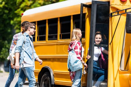 group of happy teen scholars entering school bus after lessons