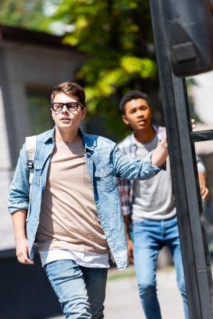 multiethnic teen schoolboys walking at school bus