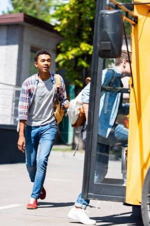 multiethnic teen schoolboys entering school bus