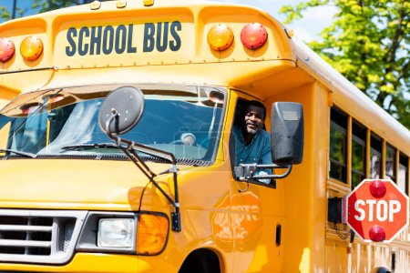 Photo for Handsome senior school bus driver looking at camera through window - Royalty Free Image