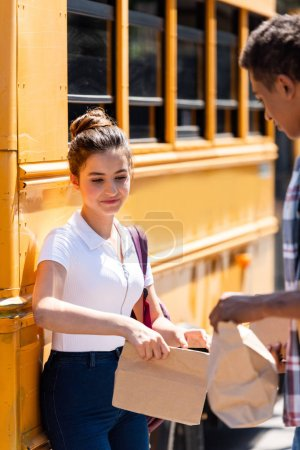 teen students holding paper bags with lunch while standing near school bus