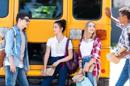 group of teen scholars spending time together while leaning on school bus