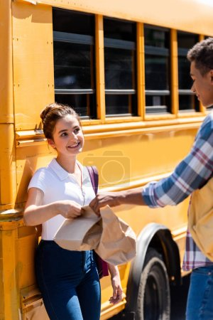 happy teen students holding paper bags with lunch while standing near school bus