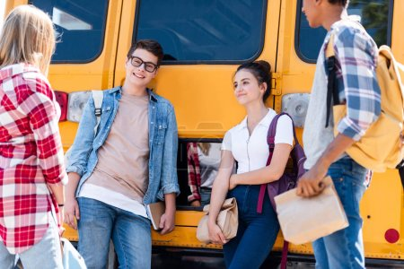 group of teen scholars chatting while leaning on school bus