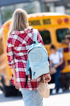 rear view of teen schoolgirl with backpack walking to classmates leaning on school bus