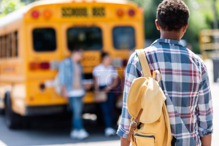 rear view of african american schoolboy walking to classmates leaning on school bus
