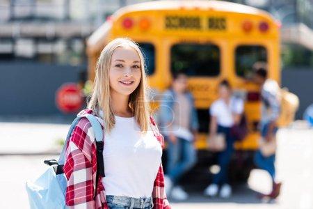 happy teen schoolgirl looking at camera in front of school bus