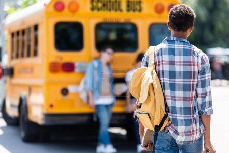 Photo pour Vue arrière de l'écolier adolescent marchant vers ses camarades de classe penché sur le bus scolaire - image libre de droit