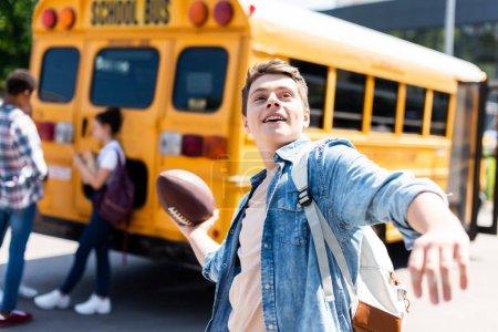écolier teen souriant, lancez une balle de football américain en face de l'autobus scolaire