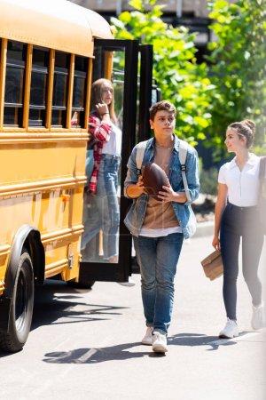 group of happy teenagers walking in front of school bus