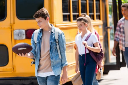 group of happy teen students walking in front of school bus
