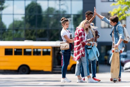 group of teen students giving high five on parking in front of school bus