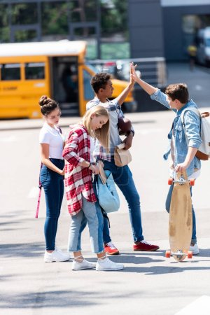 group of teen scholars giving high five on parking in front of school bus