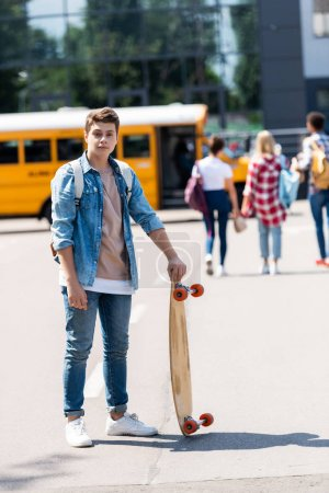 happy teen schoolboy with skateboard standing in front of school bus and group of classmates walking blurred on background