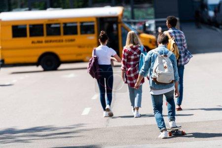 Photo pour Vue arrière du groupe d'adolescents érudits marchant jusqu'à l'autobus scolaire en stationnant - image libre de droit