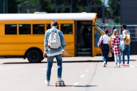 Foto de Vista trasera del colegial montar patineta por aparcamiento a sus compañeros de clase - Imagen libre de derechos