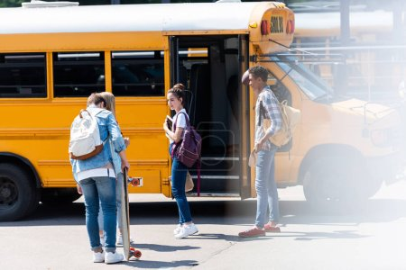 group of teen scholars standing near school bus